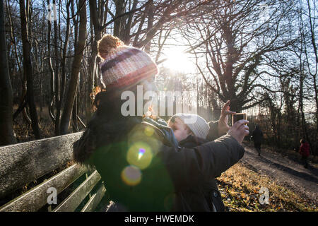 Mother sitting on bench with baby boy, taking selfie with smartphone - Stock Photo