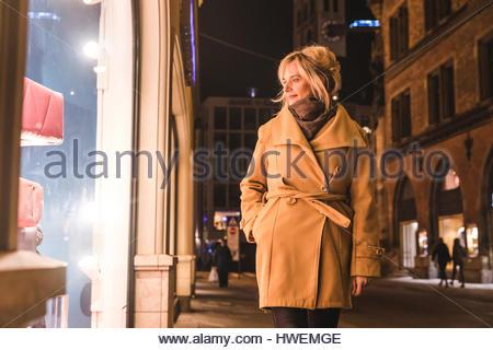 Mature woman window shopping at night, Munich, Germany - Stock Photo