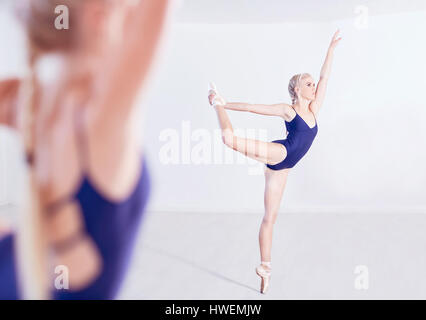Mirror image of young female ballet dancer en pointe in dance studio - Stock Photo