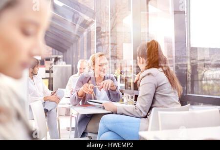 Businesswomen having discussion during working lunch in restaurant - Stock Photo