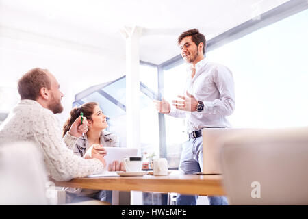 Young businessman making presentation to business team in office - Stock Photo
