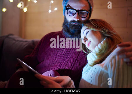 Couple using digital tablet on sofa in chalet - Stock Photo