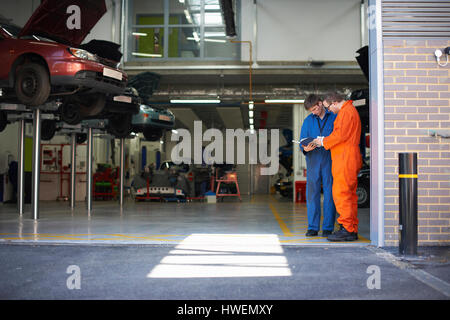 College mechanic students reading manual in repair garage - Stock Photo