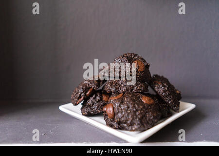 Stack of Vegan chocolate brownie cookie on white square plate - Stock Photo