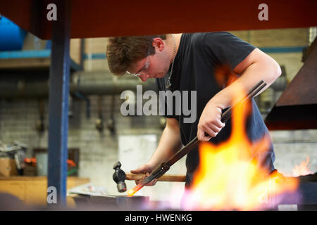 Young male trainee blacksmith hammering red hot metal on workshop anvil - Stock Photo