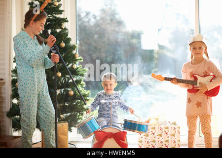 Boy and sisters playing toy drum kit and guitar on christmas day - Stock Photo