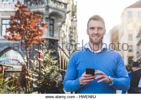Portrait of young man holding smartphone at christmas market - Stock Photo