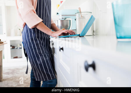 Mid section of young female baker at kitchen counter typing on laptop - Stock Photo
