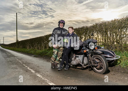 Portrait of senior male motorcyclist and grandson sitting on motorcycle at roadside - Stock Photo