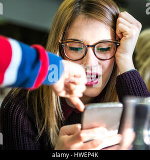 Young woman with boy's hand pointing at smartphone in cafe - Stock Photo