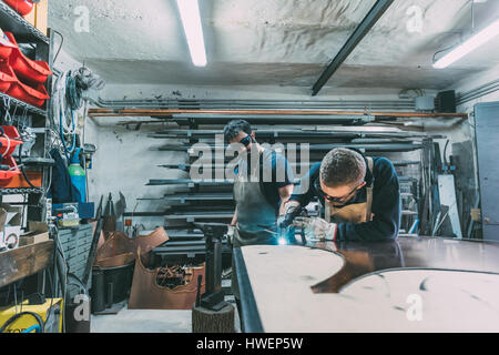 Metalworker cutting copper with welding torch in forge workshop - Stock Photo