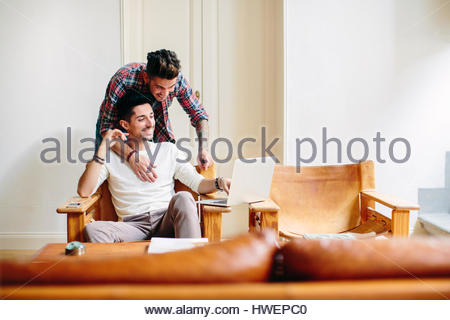 Young man at home, sitting in chair, using laptop, his partner hugging him from behind - Stock Photo