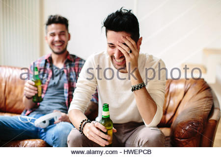 Male couple sitting on sofa, holding beer bottles, laughing - Stock Photo