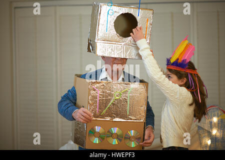 Girl in feather headdress putting robot costume onto grandfather - Stock Photo