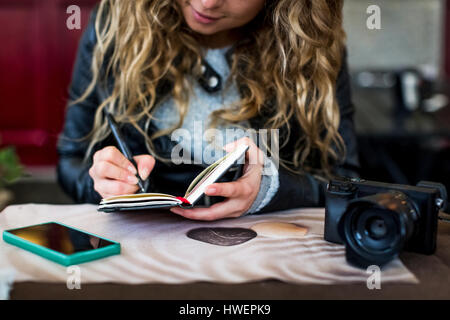 Woman at cafe writing in notebook - Stock Photo
