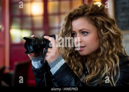 Woman using digital camera - Stock Photo