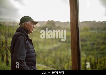Senior man looking out over vineyard  landscape