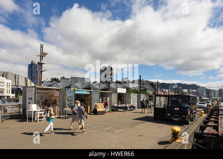 WELLINGTON, NEW ZEALAND - MARCH 2, 2017: Yound men wander aound the street market in the Wellington waterfront promenade - Stock Photo