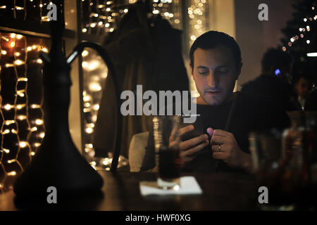 man holding hookah pipe and smoking in a night club  - Stock Photo