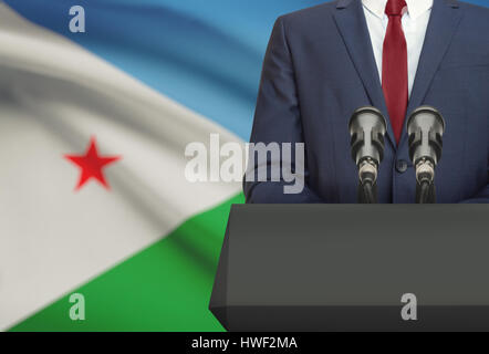 Businessman or politician making speech from behind the pulpit with national flag on background - Djibouti - Stock Photo