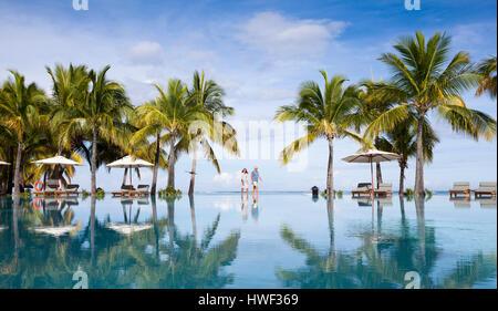 Honeymooners walking neer swimming pool. Luxurious five stars holiday resort on tropical paradise island Stock Photo