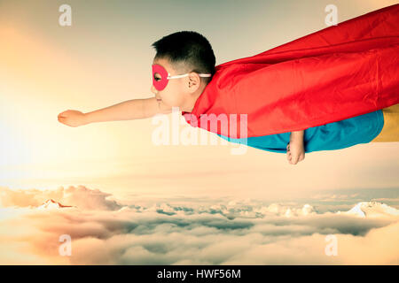 Asian Chinese boy wearing super hero costume in isolated white background. - Stock Photo