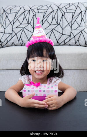 Asian Chinese little girl with gift box celebrating birthday at home indoor. - Stock Photo
