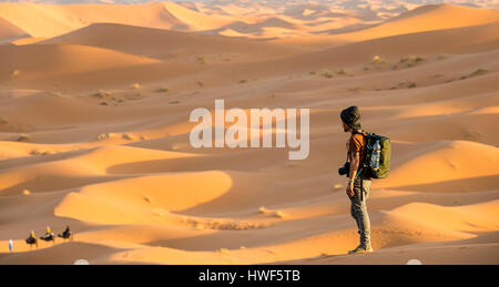 A man enjoys the view from the top of the Sahara Desert dunes at sunset - Merzouga - Morocco - Stock Photo