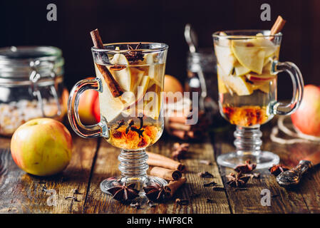 Hot Apple Cider and Ingredients on Wooden Table - Stock Photo