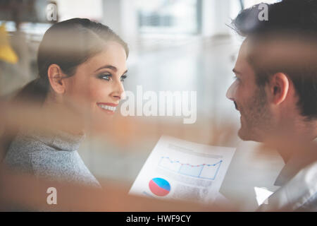 Cheerful business couple enjoying work together - Stock Photo