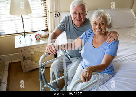 Senior man consoling woman in bedroom at home - Stock Photo