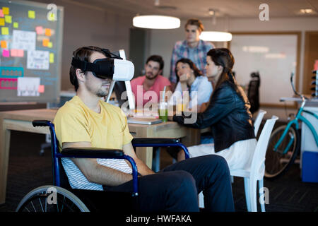 Physically disabled man on wheelchair using VR headset in office - Stock Photo