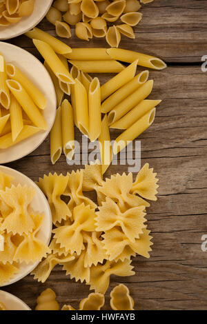 Varieties of pasta spilling out of spoons on wooden background - Stock Photo