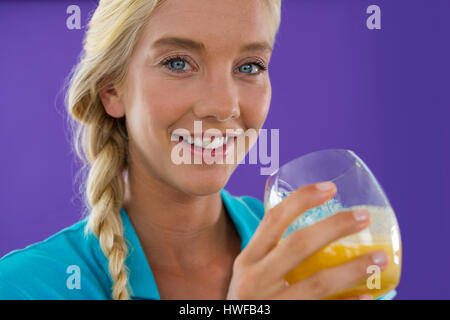 Portrait of beautiful woman holding smoothie against violet background - Stock Photo