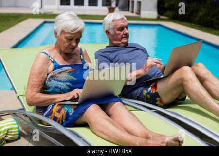 Senior couple using laptop on lounge chair at poolside - Stock Photo