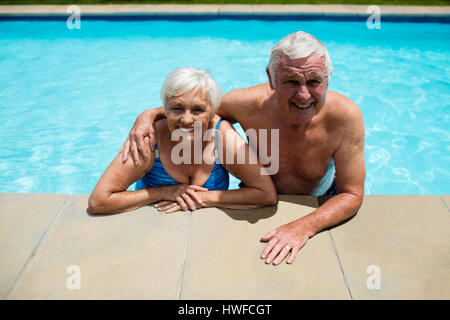 Portrait of happy senior couple relaxing together in pool - Stock Photo