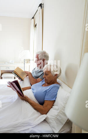 Senior couple reading books in the bedroom at home - Stock Photo
