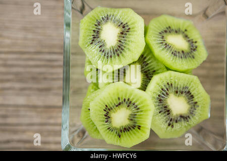 Slices of kiwi in glass bowl on wooden table - Stock Photo