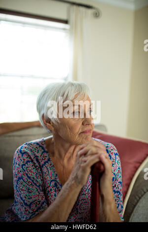 Sad senior woman sitting on couch at home - Stock Photo