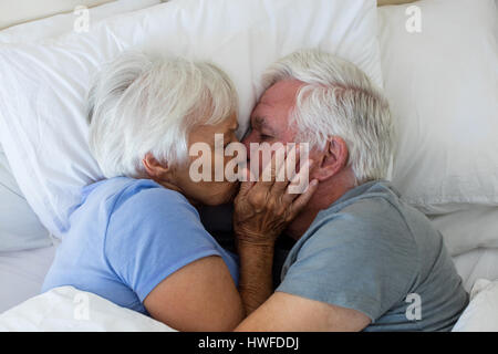 Senior couple kissing each other in bedroom at home - Stock Photo
