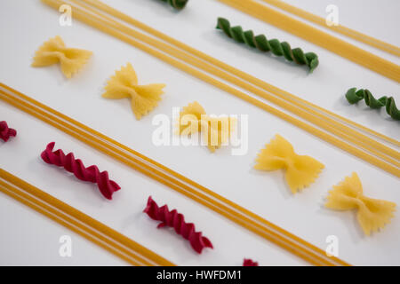 Various multicolored pasta arranged on white background - Stock Photo