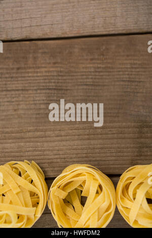 Fettuccine pasta arranged in a row on wooden background - Stock Photo