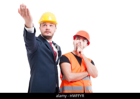 Bussinesman explaining and indicate something to young builder on white background - Stock Photo