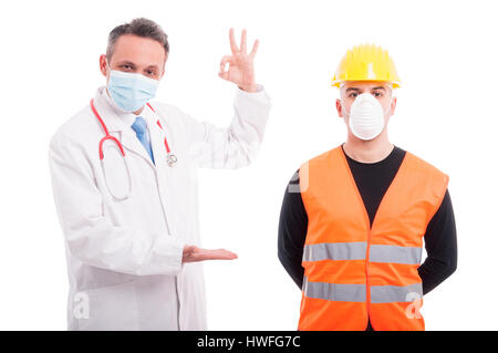 Doctor holding something and showing okay with constructor aside isolated on white background with copy text space - Stock Photo