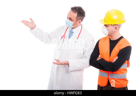 Doctor explaining something to constructor wearing marks and protection helmet isolated on white background with - Stock Photo
