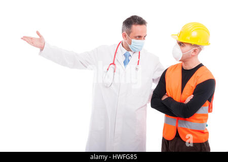 Doctor showing something to constructor wearing marks and protection helmet isolated on white background with copy - Stock Photo