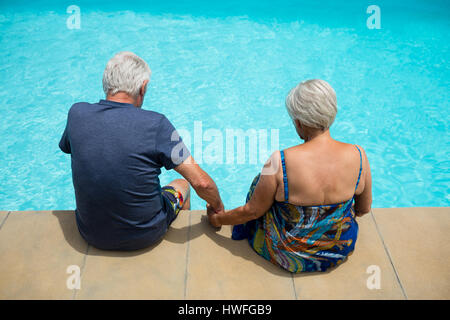 Rear view of senior couple relaxing at poolside - Stock Photo