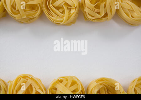 Fettuccine pasta arranged in a row on white background - Stock Photo