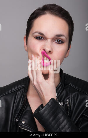 Attractive young woman wearing a leather jacket with bad expression on her face on gray background - Stock Photo