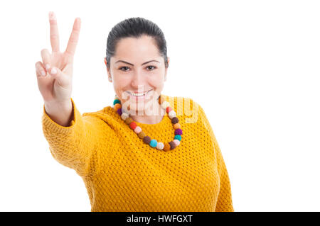 Beautiful woman doing a victory gesture and smiling on white background with copytext - Stock Photo
